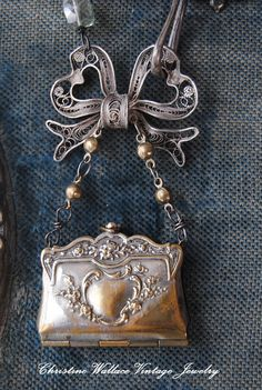 I just love the little antique French souvenir purse locket that is this necklaces main feature. It is filled with old vintage photos of famous