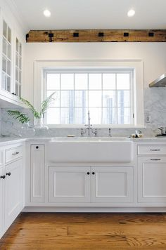 An extra wide farm sink surely stands out along with a satin nickel vintage faucet.