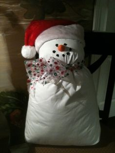 A white pillow case, a fluffy pillow, a cute little scarf, a child size santa hat, a felt orange nose, black felt dots for eyes, mouth and maybe some buttons. A little love, a little hot glue and you have the cutest little snowman pillow.