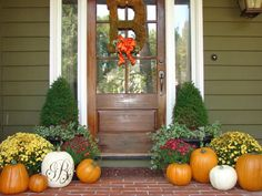 B-letter with Ribbon on Door and Snazzy Fall Front Porch Decorating Idea Plus Colourful Flowers and Mature Pumpkins