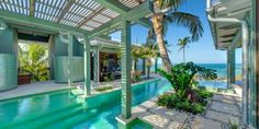 Tropical landscaping by David Young gives this beachside home with courtyard the feel of a resort. An extended two-story breezeway lies beneath the elevated pool and pergola deck, drawing visitors through the property toward the sea.
