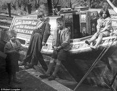 A group of children stand by a barge used to transport coal to London