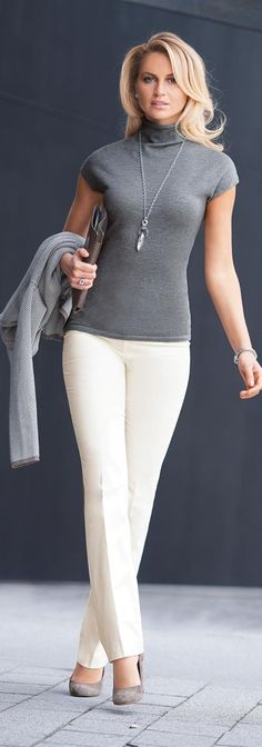 White trousers worn with grey knit top & grey & white print jacket.