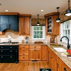 wood floor with oak cabinets with black accents
