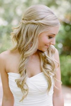 If you're looking for a faux half-up look and aren't feeling a braid, take inspiration from this 'do by Symmetry Beauty featured on Brides and simply twist two sections of hair from the front of the head to the back, and pin into place. Soft curls can be gathered to one side or left alone.