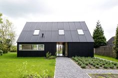 Brilliant navy blue compact home with skylights, green lawn and scandinavian style interior design. By: Kwint architecten.