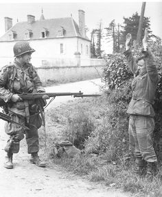 82nd Airborne trooper handling M1 Garand rifle as he captured a  German POW in Normandy during D-Day