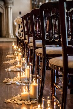 Candles surrounded by petals line the aisle for an indoor ceremony | villasiena.cc