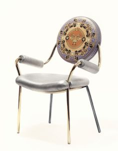"""Donatella Versace has designed for the Milan Furniture Fair 2015, """"The Cup of the Gods"""", a collection of chairs with geometric and sensual curves. Leather folder stamped with a Greek key, lamé leather seat available in gold and silver, this chair resumes with art nouveau style codes of the Italian fashion house."""