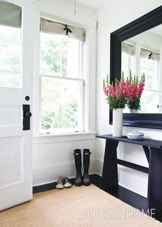 A sisal rug warms up this black-and-white entryway, while a bouquet of flowers adds a cheery pop of color. | Photographer: Janet Kimber | Designer: Deb Nelson