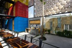 Stacked shipping containers – painted red, blue and yellow to distinguish the different room types – are arranged around a large socializing area for guests.