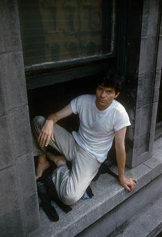 USA. New York City. 1959. Beat poet Gregory CORSO sits in the window of Alan Ginsberg's East Village apartment. Photo Burt Glinn