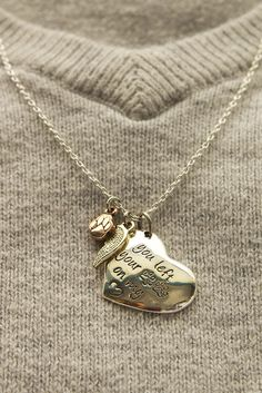 "Tell the world about the furever friend who has left an indelible print upon your heart with this charming necklace. A sweet, heart-shaped charm is adorned by a gold-tone angel wing and a copper paw print charm, with the message, ""You left your paw prints on my ♥."" Plus every purchase helps animals in need!!"