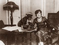 Today's picture is from 1922, and it shows a woman listening to the radio with her dog.