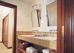 Este baño está pensado en términos dobles: sobre una mesada de cemento, bachas rectangulares acompañadas por sendos espejos luminosos con apliques.