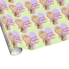 This cute Girl My 1st Valentine's Day Wrapping Paper features a pastel yellow background, a cartoon baby Girl in front of a pastel purple he...