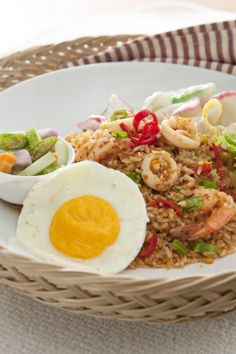 Nasi Goreng Seafood. Our seafood fried rice is sautéed with prawns, squid, and topped with fried egg.
