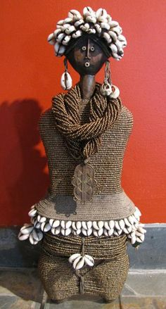 Africa | Contemporary Namji Fertility Doll from Cameroon | Handmade with glass beads, cowrie and conus shells, cotton year, brass amulets with an acrylic base.