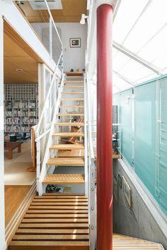 玄関を入ると、2階と地下へ続く階段が。南側の大きな傾斜窓からたっぷりと日差しが差し込む。構造上どうしても必要だった柱は、裕美さんの好きな赤に塗った。
