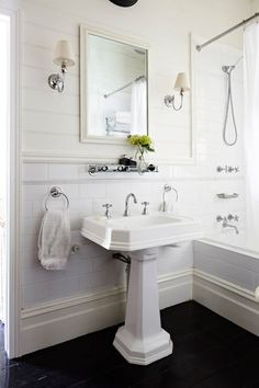Classic white bathroom design with tongue and groove panels paired with large subway tile backsplash framing ivory beveled mirror flanked by single sconces with pleated shades and vintage glass shelf over pedestal sink. White Bathroom Designs, Small Bathroom, Tongue And Groove Panelling, Bathrooms Remodel, Home, Classic Bathroom, Bathroom Design, French Provincial Bathroom, White Bathroom