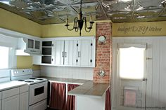 a total DIY kitchen for pennies including a tin ceiling, painted wainscotting, cabinet build, tiled counters and floors