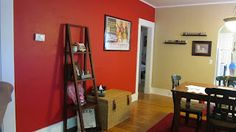 Dining room. Painted an accent wall Pomegranate (Ace Hardware). Wall brings bright and fun color to the room. The other 3 walls have a light tan to help keep the room from having too much contrast. Red pulls together the red couch from living room, red rug in dining room, and red utensils from kitchen.
