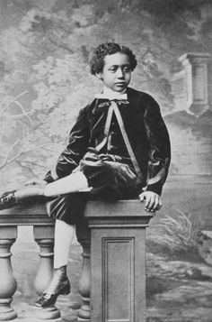 1869 - Prince Alamayou, son of King Theodore of Abyssinia, a young boy seated with legs crossed on the corner piece of a balustrade in front of a scenic backdrop. By Hughes & Mullins : Ryde, Isle of Wight (photographer). From Royal Collection