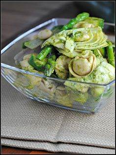 9 oz whole wheat cheese tortellini 1 bunch asparagus, cut into 2-inch pieces 2 small zucchini, sliced into 1/2-inch half moons 1/4 red onion, very roughly diced 15 oz can artichoke hearts, drained and quartered 15 oz can cannellini beans, drained and rinsed 1/3 cup prepared pesto