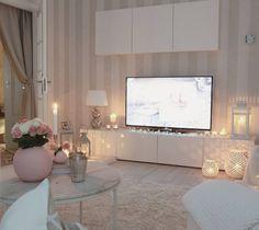 Meubles télé blanc, tapis beige et divers lanternes lumineuses...