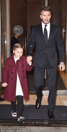 Helping hand: David Beckham held onto daughter Harper's hand arriving to his wife Victoria...