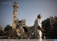 NUSSEIRAT : A Palestinian man inspects the rubble of a destroyed mosque following an Israeli military strike in the Nusseirat refugee camp in the central Gaza Strip, on July 12, 2014. Israel vowed no let-up in its aerial bombardment of Gaza, which has claimed more than 100 Palestinian lives, as a defiant Hamas rained more rockets on the Jewish state. AFP PHOTO/THOMAS COEX