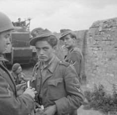 German prisoners being searched by British troops near St. Gabriel, 7th June 1944. Both men claimed to be Polish, and had Polish army badges stuck in the fronts of their field caps.