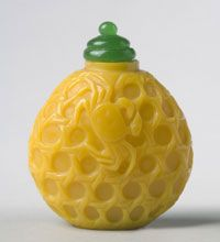 Chinese Snuff Bottle ~ Crabs in Basket ~ Qing Dynasty (1644-1911), Qianlong Period (1736-1795)Artist/maker unknown, Opaque yellow glass with carved decoration; green glass stopper with spoon ~ 2 3/4 x 2 1/2 inches (7 x 6.4 cm)