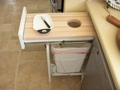 Cutting board with hole to drop scraps in trash/compost bin. I like this idea for the prep area.