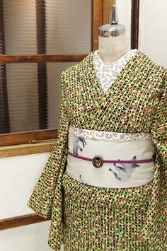 ミントグリーンの格子と、菜の花色、藤紅紫、白、紅色の砂糖菓子のようなお花模様が染め出されたレトロキュートなウールの単着物です。