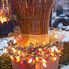 Bring new light to an old planter by adding yellow, red, and whiteChristmas lights to its base. A shimmery ribbon wrapped around branches adds an extra hint of holiday glam. Christmas Light Tip:Vintage Christmas lights are an easy way to add fun and festive flair to your outdoor decor. Use alone or pair with simple white lights. /