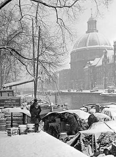 1942. The daily rigor of life disappears as the city of Amsterdam is covered by a thick layer of snow. In the photo the Singel with in the background the Ronde Lutherse Kerk or Koepelkerk. Photo Historisch Archief Community /Van Bilsen #amsterdam #1942 #singel