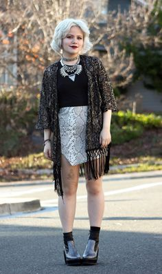 Shop this look on Lookastic:  https://lookastic.com/women/looks/open-cardigan-cropped-top-mini-skirt-boots-necklace/7515  — Black Cropped Top  — Silver Necklace  — Grey Snake Mini Skirt  — Charcoal Leather Boots  — Black Lace Open Cardigan