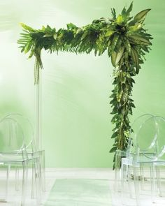 Leafy Wedding Ceremony Marker: Need proof that simple can be spectacular? Look up! This flower-free canopy requires only tropical foliage—ferns, philodendron, and jungle fronds, to be exact—to make a striking ceremony marker. Floral wire was used to wrap bunches of leaves around green-painted 4-by-4s. Asymmetry keeps it interesting, and rows of polycarbonate chairs allow for a clear view.
