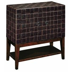 Add storage space to any room in your home with this mid-century style Maxwell chest. This handsome tapered-leg piece features two braided leather doors that open to provide space for keeping games, movies or other personal items.