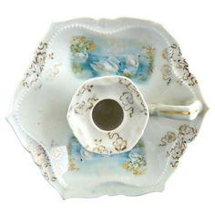 An antique porcelain chamberstick featuring swans in a lake. Each matching portrait is detailed with snowy white swans against a blue water