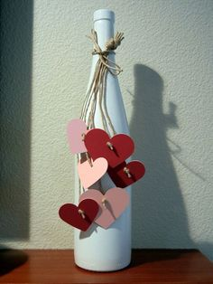 This one is great for decorations. You can find an old wine bottle, cut some little hearts on craft paper and tie them on the neck bottle with a string. Simple but filled with love.