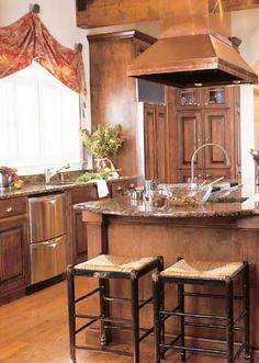 Old World Functional- Furniture-like cabinetry and natural surfaces bring old-world style to functional design. A dramatic 14-foot-high copper hood rises over a professional cooktop on the kitchen's island. Maple cabinets were stained dark and fitted with antique-look hardware and pulls.