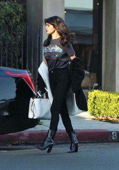Take a graphic tee and spice it up with ankle boots and a oversized jacket for a relaxed but sexy look like Selena Gomez does.
