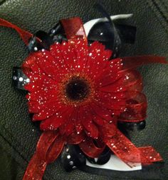 Red gerbera daisy wrist corsage embellished with silver fairy dust and matching ribbon