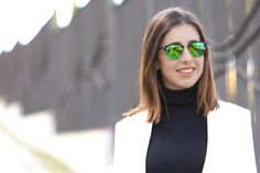 midilema.com | A touch of colour | Lucía Peris is wearing leather shorts, black ankle boots, black turtleneck sweater, white coat, and green mirror sunglasses. Casual chic. // Lucía Peris lleva pantalones cortos de cuero, jersey negro de cuello alto, botines negros, abrigo blanco y gafas verdes espejo.