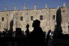 SAFE FOR NOW: A man smoking a cigarette was silhouetted in front of the Great Inn in Nicosia, Cyprus, Monday. The deal to bail out Cyprus has averted the latest threat to the breakup of the euro but at the cost of raising new questions about the common currency's long-term viability. (Yorgos Karahalis/Reuters)