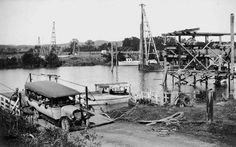 Motor bus crosses the Logan River, 1930 - Busy spot on the Logan River. A crowded bus crosses the river via the ferry 1930. Close-by, construction is underway on the road bridge which was completed in 1931.