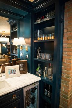 Den with a built - in bar features peacock blue cabinets adorned with brass hardware fitted with a glass-front wine cooler topped with white marble framing bar sink against a mirrored backsplash illuminated by brass sconces next to peacock blue built-in bar shelves lined with libations and gold leaf whiskey glasses.