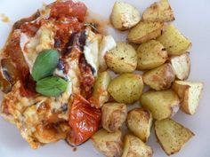 Baked aubergine with tomatoes and cheese served with baked potatoes.